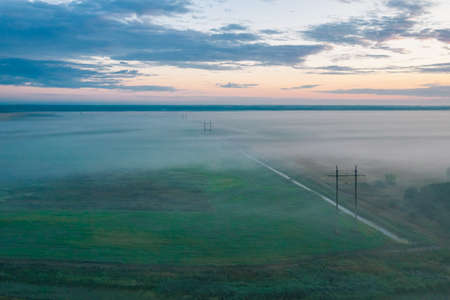 Morning summer fog in the field power line at dawn in the mystic fog 免版税图像