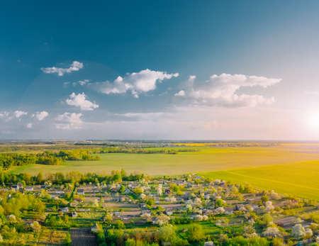 Summer cottage village landscape under blue sky with green fields. 免版税图像