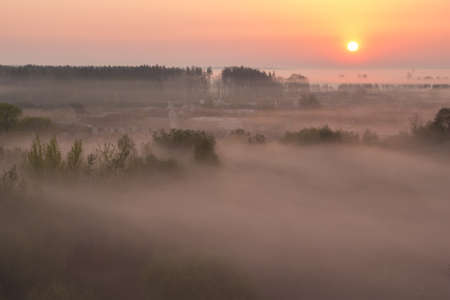 The village near the forest completely covered in mist at dawn with the rising sun over the horizon 免版税图像