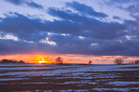 Sunset with orange sun in the clouds over snowy rural fields