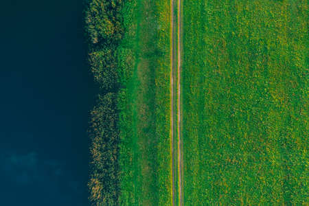Aerial view - a country road in a green summer field near the lake. Background