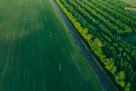 Aerial view - A beautiful flat highway in a field on one side and forest land on the other