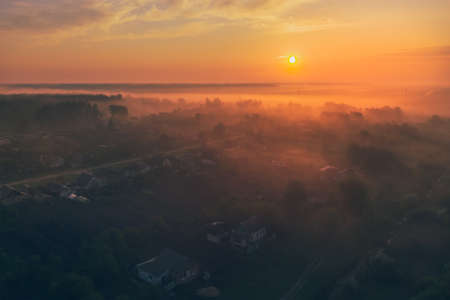 Aerial view - summer dawn in the fog over the village near the forest 免版税图像