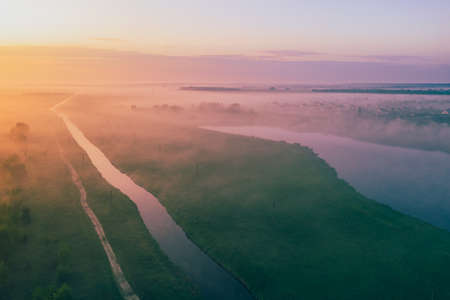 Beautiful foggy summer morning over fields with lakes and a river. View from above