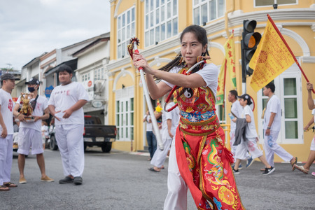"""devotee: Phuket, Thailand : - October 5, 2016: A Unidentified devotee of Phuket Vegetarian Festival, person who invites the spirits of gods to possess their bodies call """"Mah Song"""" with pierced weapon to their"""