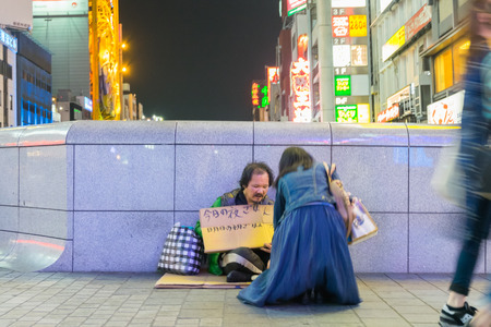 mentally ill: Osaka, Japan - April 26, 2016: Unidentified homeless man sitting on the street and asking for help