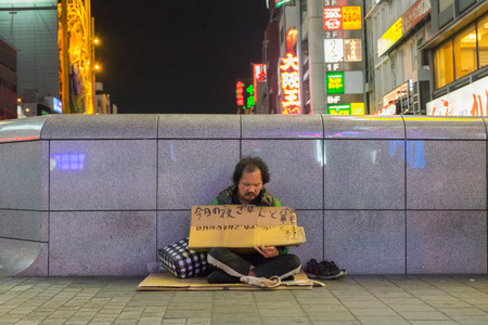 personne malade: Osaka, Japan - April 26, 2016: Unidentified homeless man sitting on the street and asking for help