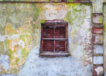 without window: The old brick wall which covered colorful damaged plaster with broken window without glass
