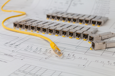 gigabit: Electric gigabit sfp modules for network switch on the blueprint of communication equipment and patch cord Stock Photo