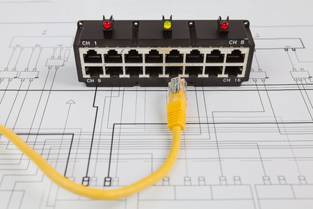 Network switch and UTP ethernet cable on the blueprint of communication equipment