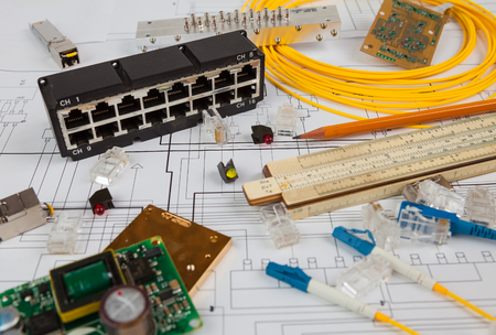 utp: Network switch, UTP ethernet and optical cable, chips and other electronic components are on the blueprint of communication equipment Stock Photo