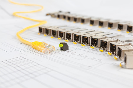 Electric gigabit sfp modules for network switch, yellow patch cord and green diod on the blueprint of communication equipment