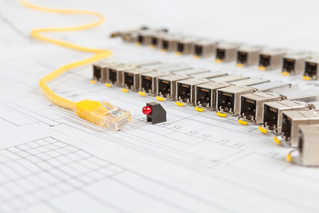 gigabit: Electric gigabit sfp modules for network switch, yellow patch cord and red diod on the blueprint of communication equipment Stock Photo
