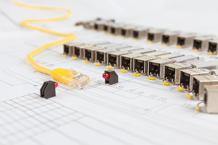 gigabit: Electric gigabit sfp modules for network switch, yellow patch cord and red diodes on the blueprint of communication equipment