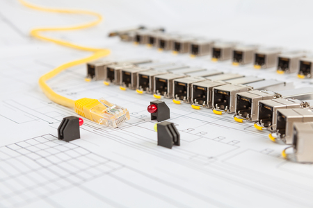 gigabit: Electric gigabit sfp modules for network switch, yellow patch cord, green and red diodes on the blueprint of communication equipment Stock Photo