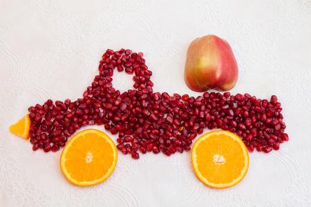 motor de carro: Las semillas de la granada y rodajas de naranja son como forma de camión con la manzana Foto de archivo
