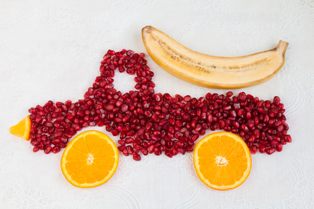 autotruck: Seeds of pomegranate and slices of orange are as shape of lorry with banana Stock Photo