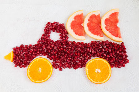 autotruck: Seeds of pomegranate and slices of orange are as shape of lorry with grapefruit
