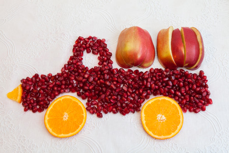 motor de carro: Seeds of pomegranate and slices of orange are as shape of lorry with apple