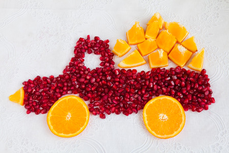 autotruck: Seeds of pomegranate and slices of orange are as shape of lorry with orange