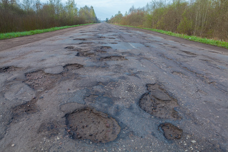 pits: Large pits and holes on the asphalts road.