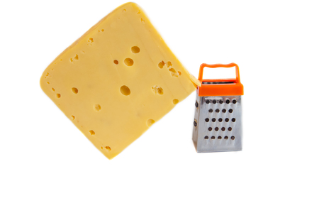 metal grate: Piece of huge cheese and tiny metal grate for preparing  grated cheese isolated on white