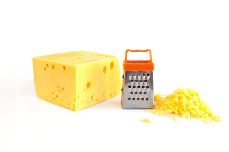 queso rallado: Pedazo de gran queso, el queso rallado y la rejilla de metal pequeña para la preparación de queso rallado aislado en blanco