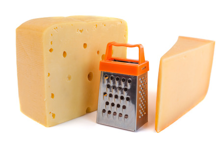 metal grater: Pieces of huge cheeses of different tastes and tiny metal grate for preparing grated cheese isolated on white