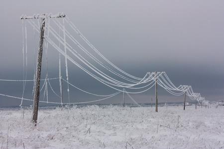 Stromleitungen der unterbrochenen Phase mit Reif auf den hölzernen elektrischen Polen auf Landschaft im Winter, Pol mit Drähten