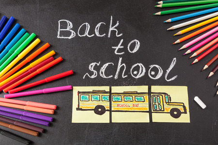 felt tip: Back to school background with colorful felt tip pens, pencils,  title Back to school written by white chalk and the school bus drawn on yellow pieces of paper on the black school chalkboard