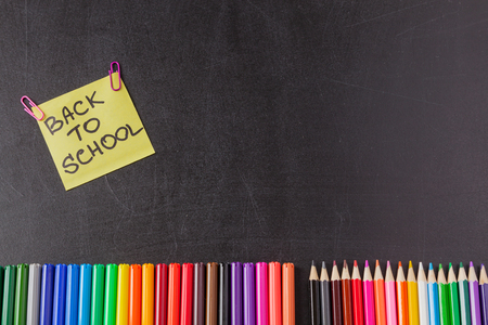 felt tip: Back to school background with colorful felt tip pens, pencils and  title Back to school written on yellow piece of paper on the black school chalkboard Stock Photo
