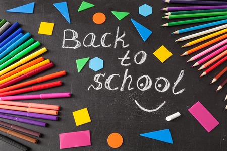 felt tip: Back to school background with colorful felt tip pens, pencils,  title Back to school written by white chalk and colorful geometric figures on the black school chalkboard