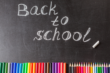 felt tip: Back to school background with colorful felt tip pens, pencils and the title Back to school written by white chalk on the black school chalkboard
