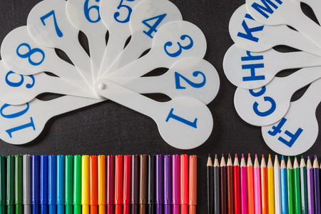 consonant: Back to school background with a lot of colorful felt-tip pens and colorful pencils and cards of numerals from one to ten and consonant letters of alphabet on the black school chalkboard Stock Photo