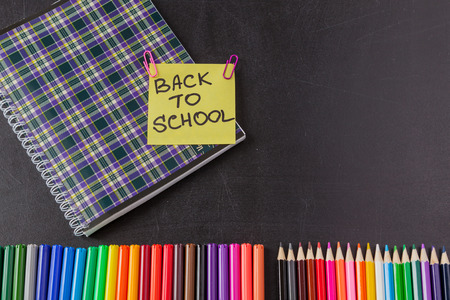 felt tip: Back to school background with colorful felt tip pens, pencils, notebook and  title Back to school written on yellow piece of paper on the black school chalkboard Stock Photo