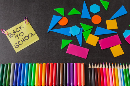 felt tip: Back to school background with colorful felt tip pens, pencils, geometric figures and  title Back to school written on yellow piece of paper on the black school chalkboard