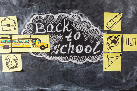handwrite: Back to school background with title Back to school  written by white chalk on the black chalkboard and the school bus drawn on yellow pieces of paper