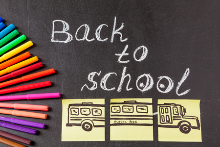 felt tip: Back to school background with colorful felt tip pens, pencils,  title Back to school written by white chalk and image of the school bus drawn on yellow pieces of paper on the black school chalkboard
