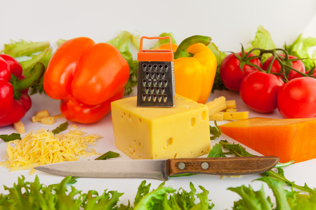 metal grate: Pieces of cheeses of different tastes, grated cheese, metal grate for preparing  grated cheese, knife,  tomatoes, peppers and leaves of frillis and arugula