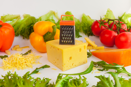 metal grate: Pieces of cheeses of different tastes, grated cheese, metal grate for preparing  grated cheese,  tomatoes, peppers and leaves of frillis and arugula