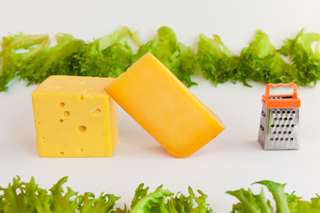 metal grate: Pieces of cheeses of different tastes, metal grate for preparing  grated cheese and leaves of frillis Stock Photo
