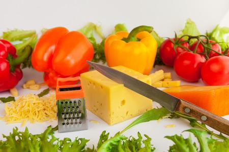 queso rallado: Los pedazos de quesos de diferentes sabores, queso rallado, rejilla de metal para la preparación de queso rallado, un cuchillo, tomates, pimientos y hojas de rúcula y frillis Foto de archivo