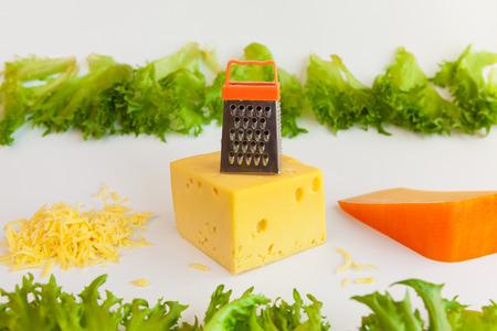 queso rallado: Los pedazos de quesos de diferentes sabores, queso rallado, rejilla de metal para la preparación de queso rallado y hojas de frillis