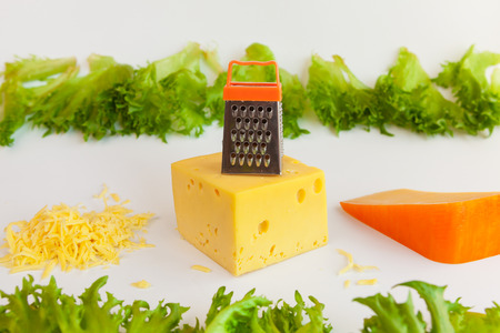 metal grate: Pieces of cheeses of different tastes, grated cheese, metal grate for preparing  grated cheese and leaves of frillis