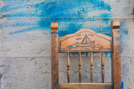 sail ship: The back of old wooden chair with drawing of sail ship and dolphin on the background concrete wall with spots of blue paint. ( close-up) Village Bali, island Crete, Greece. Stock Photo