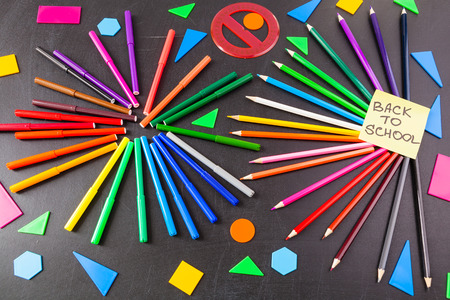 Back to school background with a lot of colorful felt-tip pens and colorful pencils in circles and  title Back to school written on the yellow pieces of paper on the black school chalkboard
