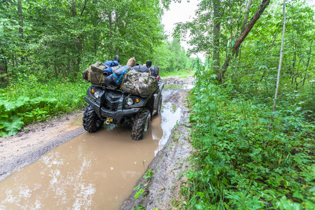 Dirty ATV stands with bags and stuff in the deep muddy puddle on the forest road Stock Photo