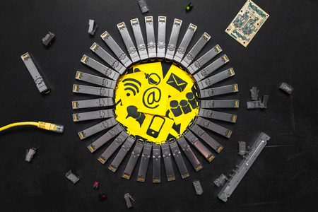 Electrical Internet SFP network modules, RJ45 ethernet cable, RJ45 connectors, circuit board with microchips, diodes and yellow stickers with  telecommunications icons are on the black background