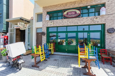 rethymno: Rethymno, Island Crete, Greece, - July 1, 2016: View of the cafe with color chairs which is located near the embankment of Mediterranean Sea