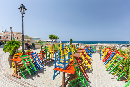 Rethymno, Island Crete, Greece, - July 1, 2016: View of the cafe with color chairs which is located near the embankment of Mediterranean Sea
